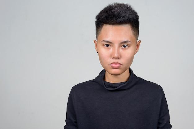 Photo de studio de jeune femme lesbienne asiatique aux cheveux courts sur fond blanc
