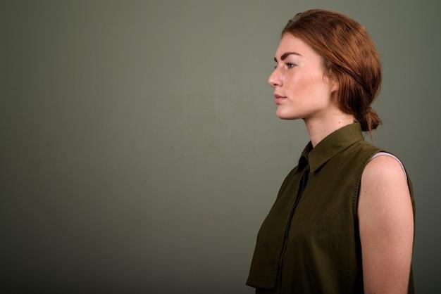 Photo de studio de jeune femme portant un haut sans manches vert sur fond coloré
