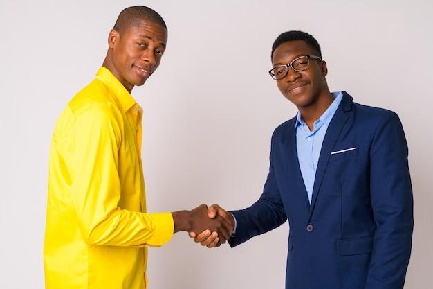 Photo de studio de jeune homme d'affaires africain chauve et jeune homme d'affaires africain ensemble sur fond blanc
