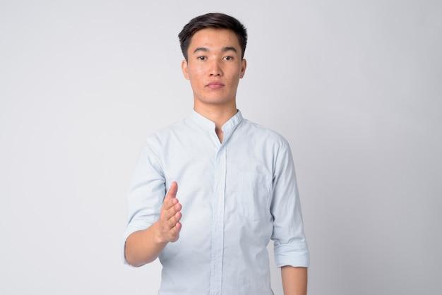 Photo de studio de jeune homme d'affaires asiatique beau sur fond blanc