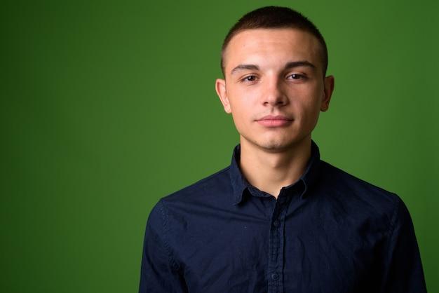 Photo de studio de jeune homme d'affaires beau contre backgrou vert