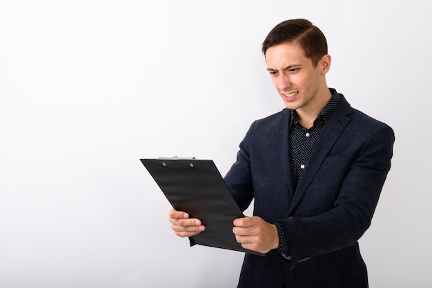 Photo de studio de jeune homme d'affaires en colère en regardant le presse-papiers agai