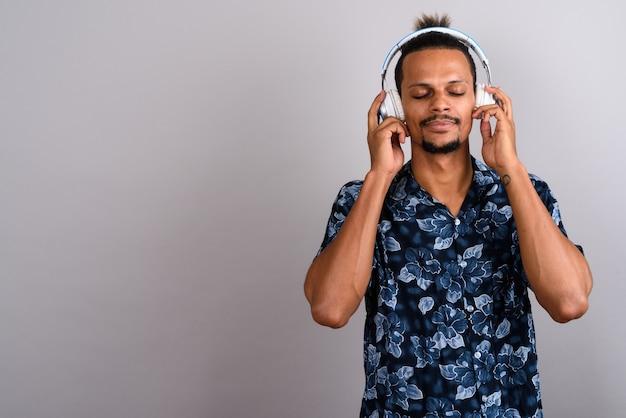 Photo de studio de jeune homme africain beau barbu portant chemise hawaïenne tout en écoutant de la musique sur fond gris
