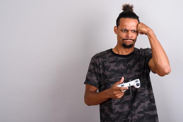 Photo de studio de jeune homme africain beau barbu portant une chemise imprimée de camouflage avec les cheveux attachés sur fond gris