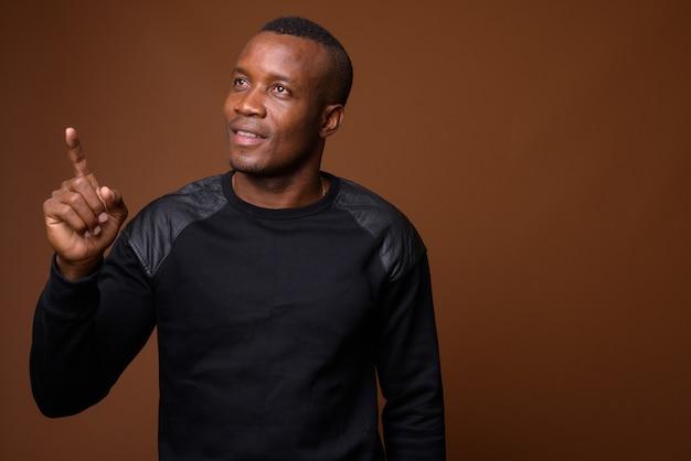 Photo de studio de jeune homme africain sur fond marron