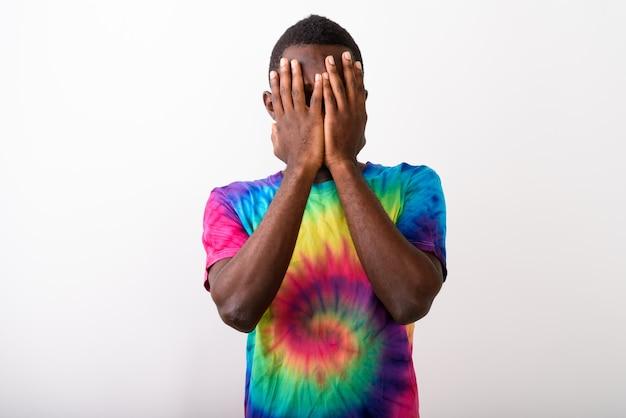 Photo de studio de jeune homme africain noir couvrant son visage avec bo