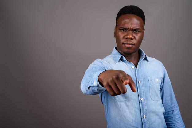 Photo de studio de jeune homme africain portant une chemise en jean sur fond gris