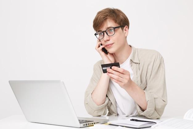 Photo de studio de jeune homme est assis à une table et regarde sur le côté à travers ses lunettes
