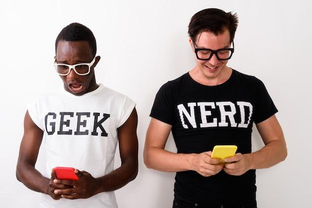 Photo de studio de jeune homme geek africain noir choqué à l'aide de mobile