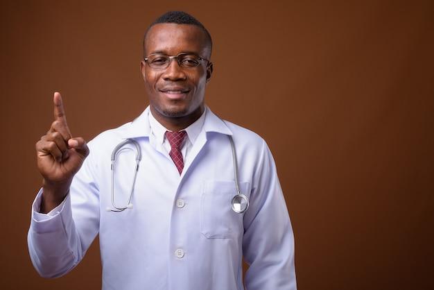 Photo de studio de jeune médecin homme africain sur fond marron