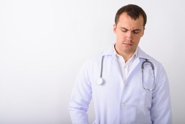 Photo de studio de jeune médecin homme musclé pensant tout en regardant
