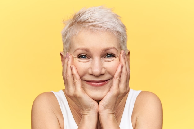 Photo de studio de jolie femme d'âge moyen drôle avec des cheveux courts teints souriant, plaçant les joues sur les mains, regardant la caméra avec une expression faciale curieuse et heureuse, voyant quelque chose de très intéressant