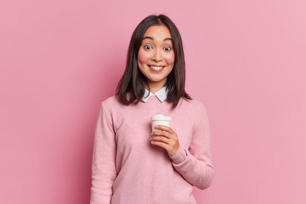 Photo de studio de jolie fille asiatique brune a pause-café sourit doucement à la caméra montre des dents blanches vêtues de poses de cavalier occasionnel en studio