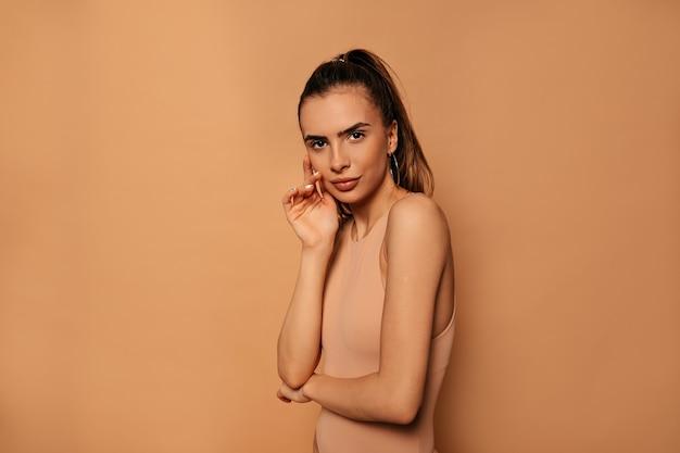 Photo de studio de jolie jeune femme aux cheveux collectés portant un corps beige posant sur un mur beige
