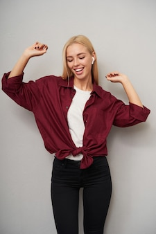 Photo de studio de jolie jeune femme blonde aux cheveux longs en bonne forme physique, écouter de la musique avec des écouteurs et danser joyeusement, debout sur fond gris clair dans des vêtements décontractés