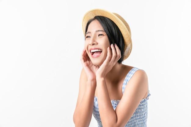 Photo de studio de joyeuse belle femme asiatique en robe de couleur bleue et portant un chapeau et se tenir debout sur fond blanc.