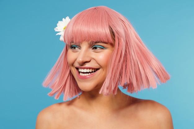 Photo de studio de joyeuse jeune femme belle portant une fleur blanche dans ses courts cheveux roses tout en posant sur fond bleu, riant joyeusement en regardant de côté