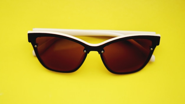 Photo de studio de lunettes de soleil. l'été arrive concept - surface jaune