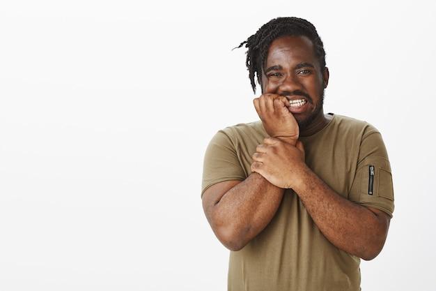 Photo de studio d'un mec anxieux dans un t-shirt marron posant contre le mur blanc