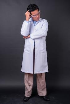 Photo de studio de médecin homme indien mature sur fond noir