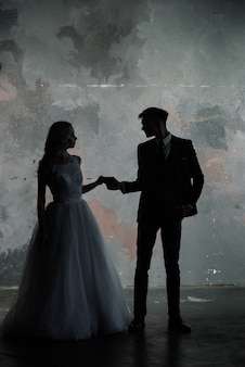 Photo de studio de mode art du marié et de la mariée silhouette couple mariage sur fond de couleurs. style de mariage d'art.