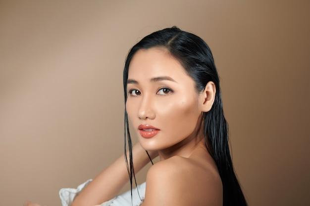 Photo de studio de mode d'une femme sexy magnifique avec des cheveux noirs luxueux sur fond beige