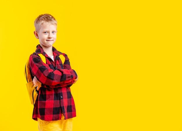 Photo de studio de petit écolier confiant, les bras croisés sur fond jaune