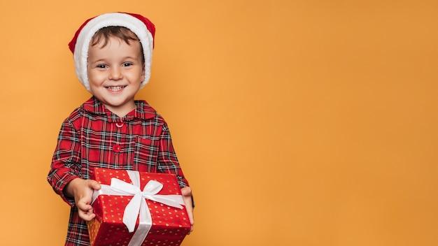 Photo de studio d'un petit garçon en pyjama de noël et un chapeau sur fond jaune avec une boîte cadeau rouge vif dans ses mains. une place pour votre texte, publicité.