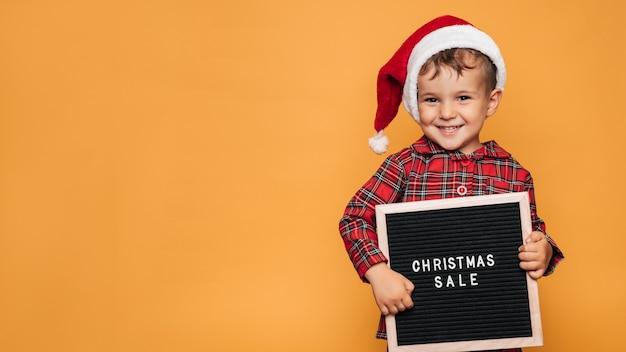 Photo en studio d'un petit garçon en pyjama de noël et d'un chapeau sur fond jaune avec un tableau à lettres avec le texte joyeux noël dans les mains. une place pour votre texte, publicité.