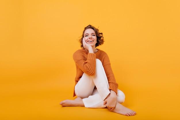 Photo de studio de rire femme magnifique posant avec les jambes croisées
