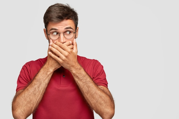 Photo de studio de secret jeune homme aux cheveux noirs couvre la bouche avec les deux mains