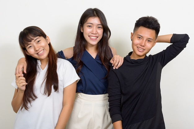 Photo de studio de trois belles jeunes femmes asiatiques en tant qu'amis ensemble sur fond blanc