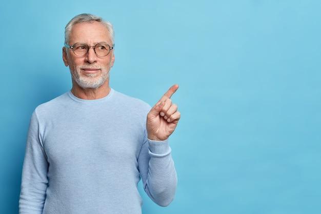 Photo de studio d'un vieil homme européen barbu satisfait aux cheveux gris donne une recommandation suggère d'utiliser cet espace de copie pour votre publicité vêtu d'un pull décontracté isolé sur un mur bleu