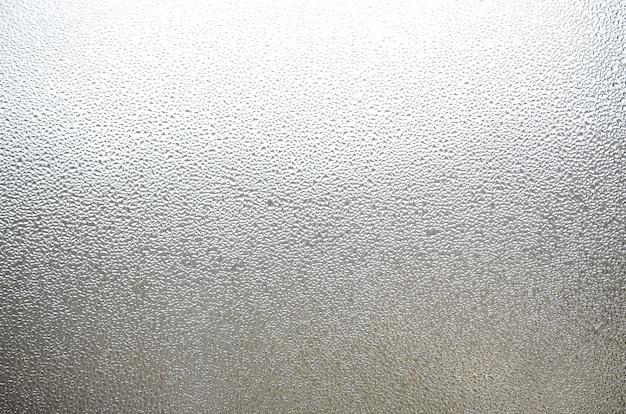 Une photo de la surface en verre de la fenêtre, recouverte d'une multitude de gouttelettes de différentes tailles. texture de fond d'une couche dense de condensat sur le verre