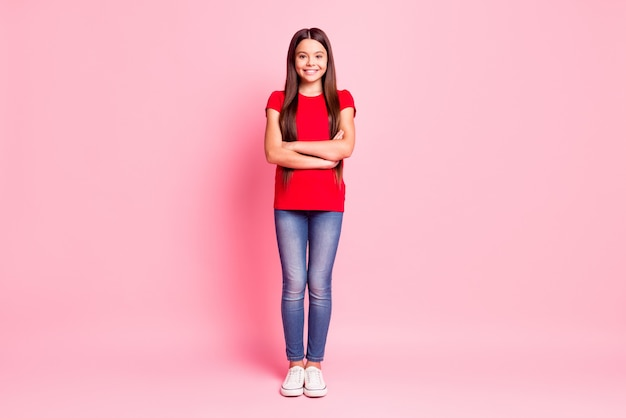 Photo de la taille complète du corps d'une jolie petite dame aux cheveux longs, aux mains croisées, confiante, sûre d'elle, souriante, souriante, porter un t-shirt rouge décontracté, des baskets de jeans, isolées, fond de couleur rose