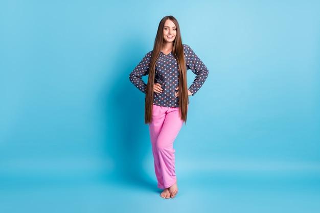 Photo de la taille du corps entier d'une charmante jeune fille souriante, mains, hanches, pieds nus, préparer les procédures du matin, porter des pyjamas en chemise à pois, vêtements de nuit isolés, fond de couleur bleu vif