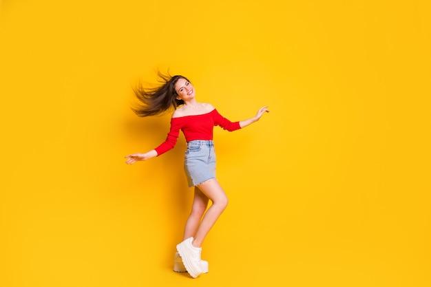 Photo de la taille du corps entier de la charmante jolie jeune fille aéré la fête de la danse des cheveux célébrant l'usure de la chemise épaules ouvertes denim mini jupe baskets isolées fond de couleur jaune vif