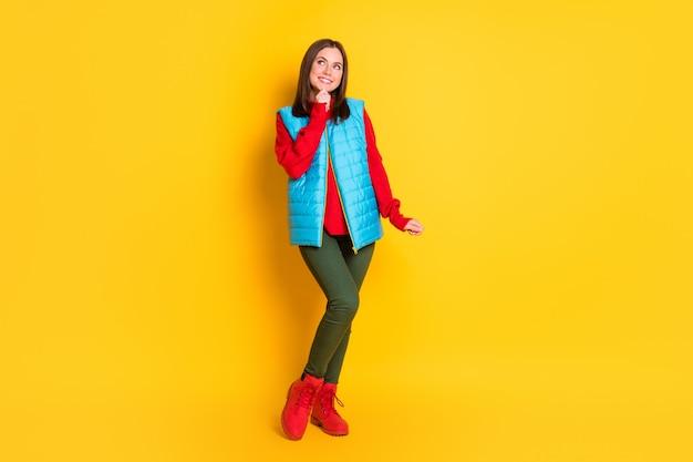 Photo de la taille du corps entier d'une jolie jeune femme au look rêveur, espace vide, menton de la main, souriant, jeune fille, posant, porter un pantalon vert, gilet bleu, pull rouge, bottes isolées, fond de couleur jaune vif