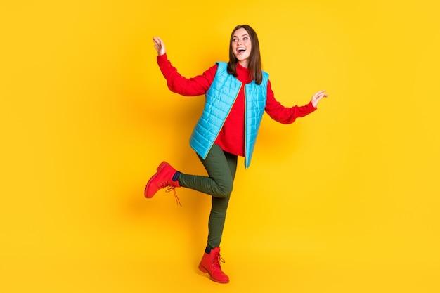 Photo de la taille du corps entier d'une jolie jeune femme souriante souriante rechercher un espace vide club de danse fête porter un pantalon vert gilet bleu pull rouge bottes isolées fond de couleur jaune vif