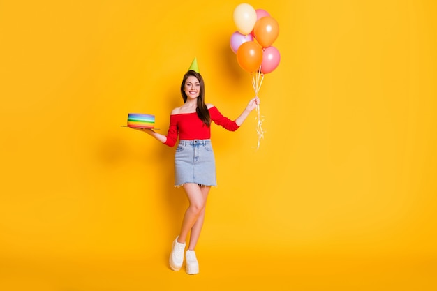 Photo de la taille du corps entier d'une jolie jolie charmante jeune fille rayonnante souriante tenir ballons gâteau porter cône chemise épaules ouvertes denim mini baskets jupe isolé fond de couleur jaune vif