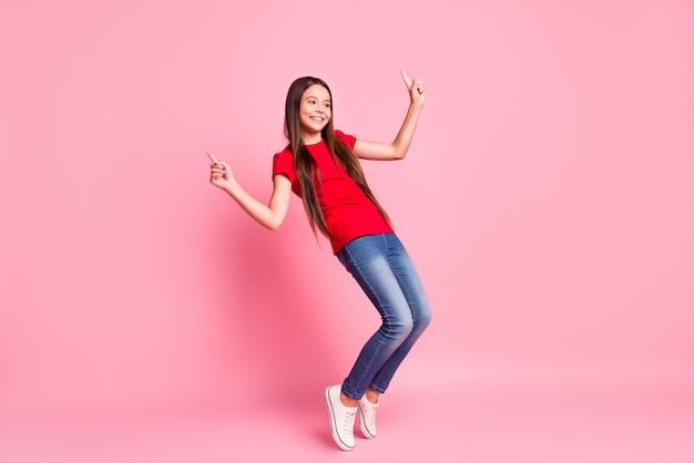 Photo de la taille du corps entier de la jolie petite dame douce coiffure longue performance danse lever la main doigt à pleines dents sourire pointe des pieds porter un t-shirt rouge décontracté jeans baskets isolé fond de couleur rose