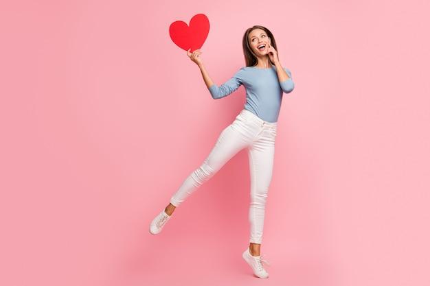 Photo de taille du corps pleine longueur de joyeuse jolie fille charmante positive excitée d'être douée en forme de grand coeur rouge en pull bleu isolé fond de couleur pastel