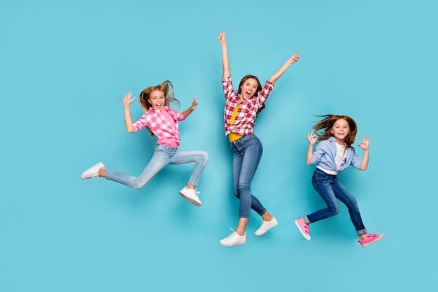 Photo de la taille du corps sur toute la longueur de la belle famille blanche joyeuse profitant de leur vie portant des jeans en denim avec désinvolture tout en isolé avec fond bleu