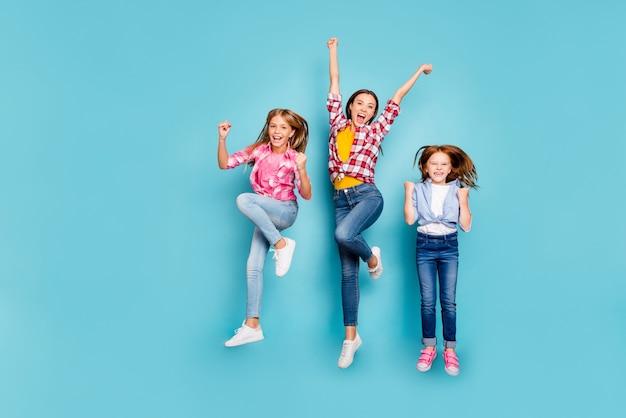 Photo de la taille du corps sur toute la longueur de la famille blanche décontractée se réjouissant d'avoir visiblement gagné quelque chose portant des jeans en denim tout en isolé avec un fond bleu