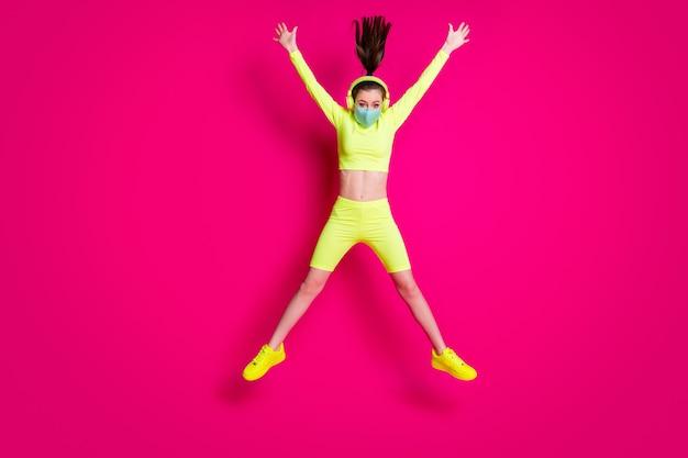 Photo de la taille du corps sur toute la longueur d'une fille sautant comme une étoile portant un casque de sport jaune isolé sur fond de couleur fuchsia lumineux