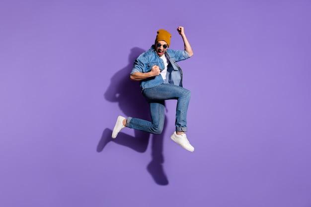 Photo de la taille du corps sur toute la longueur de gai mec hurlant extatique portant des jeans veste en jean ravi de gloire victorieuse sautant vers le haut casquette marron isolé sur fond de couleur vive violet