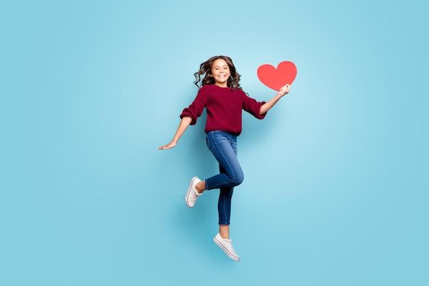 Photo de taille du corps sur toute la longueur de joyeuse belle petite amie ondulée bouclés tenant une grande carte postale rouge souriant à pleines dents chaussures couleur vive isolé fond bleu