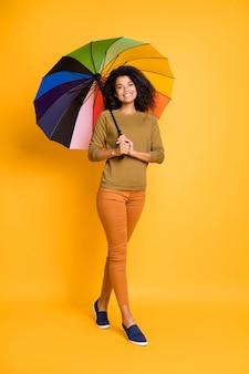 Photo de taille du corps vertical pleine longueur de joyeuse jolie petite amie positive ondulée bouclés portant des pantalons pantalons chaussures orange isolé sur fond de couleur jaune vif