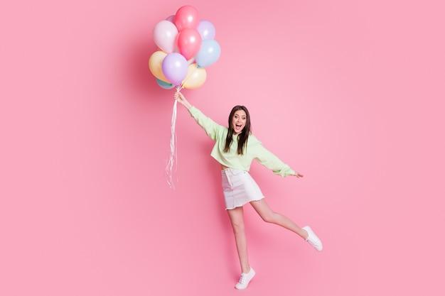 Photo en taille réelle d'une charmante dame tenant de nombreux ballons à air s'élevant dans l'air volant ravie de porter des vêtements décontractés verts pull-over jeans mini jupe chaussures isolés fond de couleur pastel rose