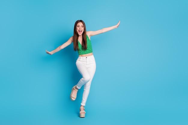 Photo en taille réelle d'une fille folle et candide profitez du week-end de temps libre pour vous réjouir, imaginez qu'elle vole un avion porter un singulet isolé sur un fond de couleur bleue